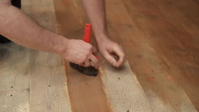 Master using broad brush causes the brown paint on the wooden floor. A man holding a red tool that paints the surface of the boards. Quickly makes movement stock video footage