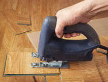 Master using an electric jigsaw saws laminated panel Stock Image