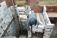 The master, using a trowel, glues gasblocks with a glutinous solution at the construction site stock photo