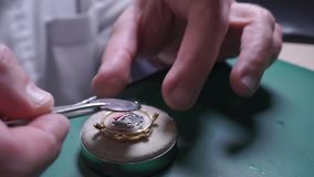 Master at watch repair shop putting down watch back cover stock video