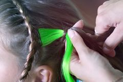 The master weaves a colored strand into the girl& x27;s braid stock image