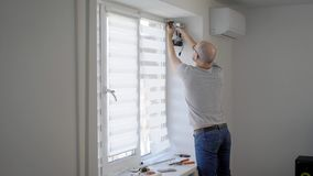 Master of window installing is using electro screwdriver for rotating screw in a frame in white light room in home. Taking details from windowsill stock footage