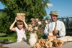 Master of wooden products with granddaughter Royalty Free Stock Photos