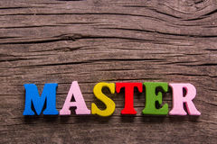 Master word made of wooden letters. Master word made from colored wooden letters on an old table. Concept Royalty Free Stock Photos