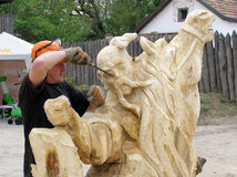 Master works above creation of wooden sculpture Royalty Free Stock Photos
