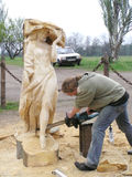 Master works above creation of wooden sculpture Stock Image