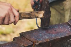 Master works on the anvil. Blacksmith forges detail. Blacksmith working outdoors. Master works on the anvil. Forging hammer of metal structures in the open air Stock Photos