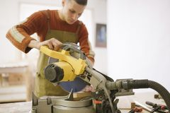 Master works as a circular saw in the carpentry workshop stock photo