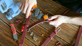 Master works with hole punch and piece of leather. On brown wooden table scattered with tools and accessories. stock video