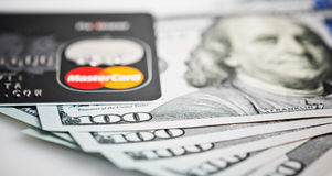 Mastercard Debit Card Over Dollar bills Stock Image