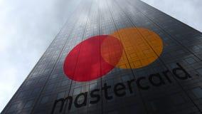 Mastercard-embleem op een wolkenkrabbervoorgevel die op wolken wijzen Het redactie 3D teruggeven Royalty-vrije Stock Foto's