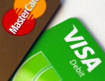 MasterCard Gold and Visa Debit Cards in a Closeup. Closeup of a Visa debit card and MasterCard Gold card. Symbols of wealth and modern financial business royalty free stock photos