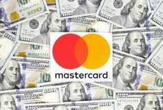 Mastercard logo printed on paper, cut and placed on money background stock image