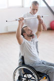 Masterful aged general practitioner training the disabled in the gym Royalty Free Stock Photos