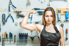 Masterful craftswoman demonstrating her biceps in the workshop Stock Photography
