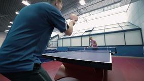 Masterly man playing a table tennis with woman at the court. Shooting from the down, man in close-up. Young man and woman virtuosity playing a table tennis at stock video footage