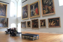 Masterpieces arranged on walls, with simple benches and people admiring, The Louvre,Paris,2016 Stock Image