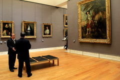 Masterpieces hanging on walls throughout rooms, with volunteers ready to answer questions,The Louvre,Paris,France,2016. Rooms with priceless masterpieces hanging Stock Photography