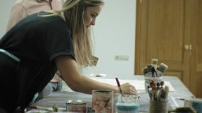Masters in the art studio process the wood with paint and putty, achieve the aging effect. Masters in the art studio process the wood with paint and putty stock video footage