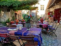 Masters Courtyard is an idyllic traditional tourist attraction in old medieval town of Tallinn, Estonia. Coffee tables outdoors. stock photo