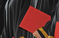 Masters degree. A detail of a figure dressed in a black academic dress holding a red diploma (a diploma with distinction). - width stock photography