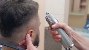 Masters hands cutting males hair with clipper and comb, close shot. Hair cutting process, recorded in barbershop. Selective soft focus. Blurred background stock video
