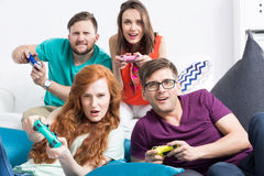 Masters of video games. Group of friends playing together video games, sitting on modern poufs, light background Stock Images