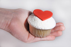 Mastic cupcake with heard on female hand Royalty Free Stock Photography