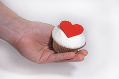 Mastic cupcake with heard on female hand. Sweet mastic cupcake with heard on female hand Royalty Free Stock Photos