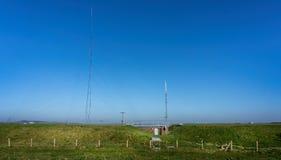 Mastro alto das telecomunicações fixado por fios do apoio na parte superior do monte branco da folha em Wiltshire, Reino Unido imagem de stock