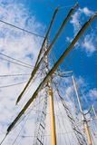 Masts against blue sky. Tall sailing ships masts and yards against a cloudy blue sky stock photos