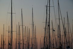 Masts. Of boats at sunset in a harbor royalty free stock image