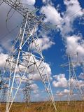 Masts of electric mains and cloudy sky Stock Photography