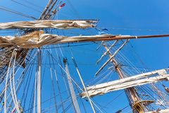 Masts of an old sailing ship with rolled up white sails royalty free stock images