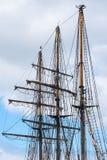Masts and rigging of a historic three-master sailing ship agains Stock Image