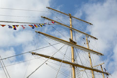Masts and rigging of a sailing ship. With flags, against blue sky and clouds. Bottom-up view. Travel concept Stock Photos