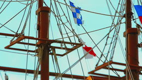 Masts and rigging of three-masted sailing ship over the bright blue sky. Close-up panning view. stock video footage