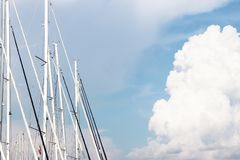 Masts of sailing yachts against the blue sky illuminated by the bright sun. Technologies of sailing and cruise charter flights. Modern marine technology for stock photography