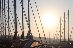 Masts of sailing yachts against the blue sky illuminated by the bright sun. Technologies of sailing and cruise charter flights. Modern marine technology for royalty free stock images