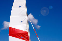 Masts and sails. On a catamaran or ship with sun flare against deep sky background royalty free stock images