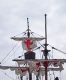 The masts sails and rigging of the santa maria a historic sailing ship in funchal harbour with white sails with red crosses. Against a blue cloudy sky royalty free stock photography