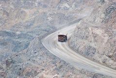 Masywny usyp ciężarówki ruszać się zjazdowy na whide i stromej drodze obrazy royalty free