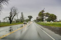 Maszeruje 20, 2017 Gilroy/CA/USA - Jadący przez deszczu na mokrej drodze zdjęcie royalty free