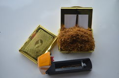 Maszyna dla wypełniać papierosy na stole z i tabakierce z tytoniem w nim żółtym deklem i niektóre tytoniem w nim Fotografia Stock