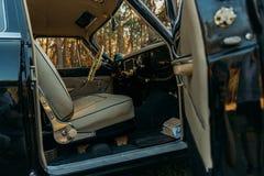 Maszynowy czerń wśrodku siedzenia beżowa skóra, retro samochód scena w lecie kierowcy ` s siedzenie, biała kierownica opłaty dla  fotografia stock