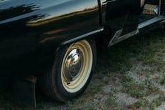 Maszynowy czerń wśrodku siedzenia beżowa skóra, retro samochód scena w lecie tylni prawa strona stara samochodowa opona, kapiszon obraz royalty free