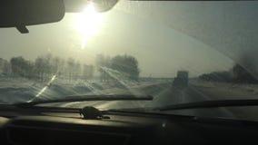 Maszynowy poruszający na zimy śnieżystej drodze z widokami zmierzch i promieniami słońce wipers wyciera brudnego zbiory