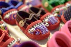 Matérias têxteis em sapatas de bebê da tenda do mercado de s imagens de stock