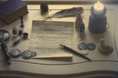 Matériaux d'écriture antiques et une bougie sur la table photographie stock