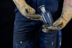 Matériaux dangereux et acides Bouteille acide maintenue dans les gants par C.A. image libre de droits